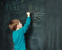 Little boy is drawing on a blackdoard Stock Photography
