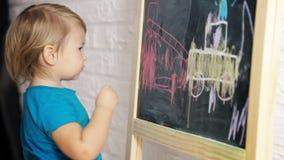 Little Boy Drawing with Chalk on Blackboard stock video footage