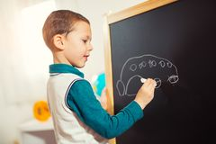 Little boy drawing with chalk on blackboard. Stock Image