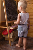 Little boy drawing with chalk on a blackboard Stock Image