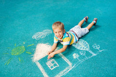 Little boy drawing chalk image on the ground Royalty Free Stock Photo