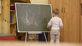 Little boy drawing on a chalkboard at kindergarten Royalty Free Stock Photo