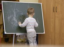 Little boy drawing on a chalkboard at kindergarten Royalty Free Stock Images