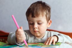 Little boy drawing with color pencils royalty free stock photography