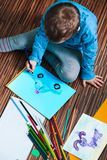 Little boy drawing a colorful picture of a car using pencil cray Stock Photography