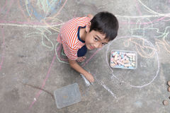 Little boy drawing and coloring by chalk on the floor Stock Images