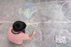 Little boy drawing and coloring by chalk on the ground art activity Stock Images