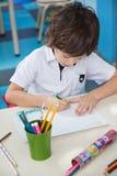 Little Boy Drawing At Desk In Art Class. High angle view of little boy drawing at desk in art class stock photo