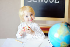 Little boy drawing and eating apple at workplace Royalty Free Stock Photo