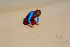 Little boy drawing family on the beach Stock Photos
