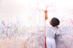 Little boy drawing happy family. On the wall Royalty Free Stock Images