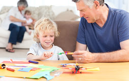 Little boy drawing with his grand father. At home stock image