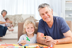 Little boy drawing with his grand father. At home stock photos