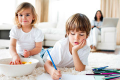Little boy drawing and his sister eating chips. Serious little boy drawing and his sister eating chips lying on the floor Royalty Free Stock Image
