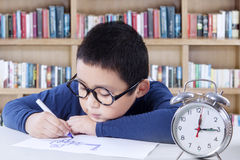 Little boy drawing in library with a clock on desk Stock Image
