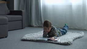 Little boy drawing while lying on floor at home stock video footage