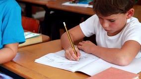 Little boy drawing in notepad in classroom. In elementary school stock video