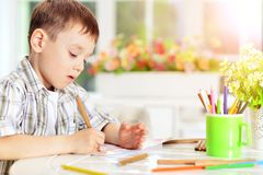 Little boy drawing with pencil. Portrait of cute little boy drawing with pencil Royalty Free Stock Image