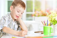 Little boy drawing with pencil. Portrait of cute little boy drawing with pencil Royalty Free Stock Images