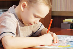 Little boy is drawing with pencils in a copybook Stock Images