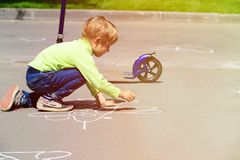 Little boy drawing plane on asphalt outdoors Royalty Free Stock Image