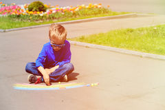 Little boy drawing rainbow with chalks on a street Stock Photos
