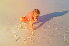 Little boy drawing sun on sand beach Royalty Free Stock Image