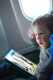 Little boy drawing on a tablet in an airplane. Little boy sitting in his seat during a flight and painting on a tablet computer in an airplane Stock Photo