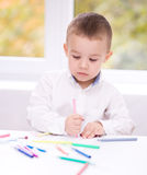 Little boy is drawing on white paper. Using color pencils Royalty Free Stock Image