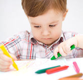 Little boy is drawing on white paper stock photos