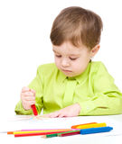 Little boy is drawing on white paper using crayon Royalty Free Stock Photography