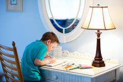 Little boy drawing or writing. Portrait of cute happy schoolkid at home drawing or writing stock photo