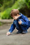 The little boy draws on asphalt Stock Photos