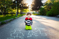 Little boy draws on asphalt. Stock Photo