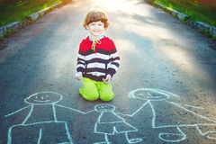 Little boy draws on asphalt in summer park. Child draws on asphalt in summer park royalty free stock images