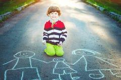 Little boy draws on asphalt in summer park. Royalty Free Stock Images