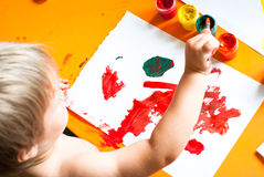 Little boy draws. A brush and paint his first picture. Focus at the drawing Stock Image