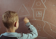Little boy draws with chalk on a blackboard, Royalty Free Stock Images