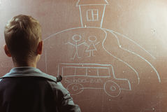 Little boy draws with chalk on a blackboard, Royalty Free Stock Image