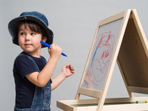 Little boy draws chalk on a school board. On the school board drawing of the child Royalty Free Stock Image