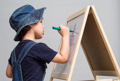 Little boy draws chalk on a school board. On the school board drawing of the child Royalty Free Stock Photos