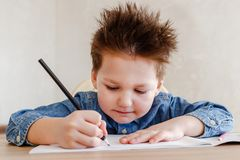 Little boy draws with a color pencil at the table royalty free stock photos