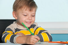 Little boy draws at the desk Royalty Free Stock Image