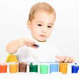 Little boy draws fingers with paint Stock Photos