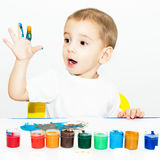 Little boy draws fingers with paint Stock Images