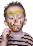 A little boy draws on the nose with a brush Stock Images