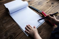 Little boy draws. On white paper with colored pencils Stock Images