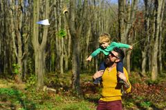 Little boy dream to fly high on fathers shoulder. Father and son launch paper plane in park. No matter what else happens royalty free stock image