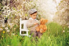 A little boy dreamer is sitting on white table with a teddy bear in a blooming cherry orchard. stock image