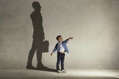The little boy dreaming about businessman profession. The little boy dreaming about businessman or diplomat profession. Childhood and dream concept. Conceptual stock photo